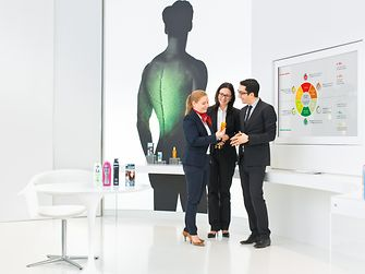 Three employees discussing in the Beauty Care Lighthouse.