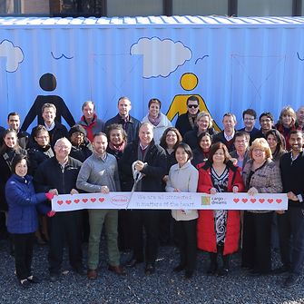 Cargo of Dreams committee members and volunteers prepare to cut the ribbon at the Dec. 14 event.