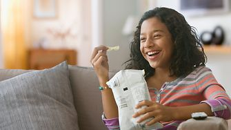 A laughing girl eating potato chips out of a bag