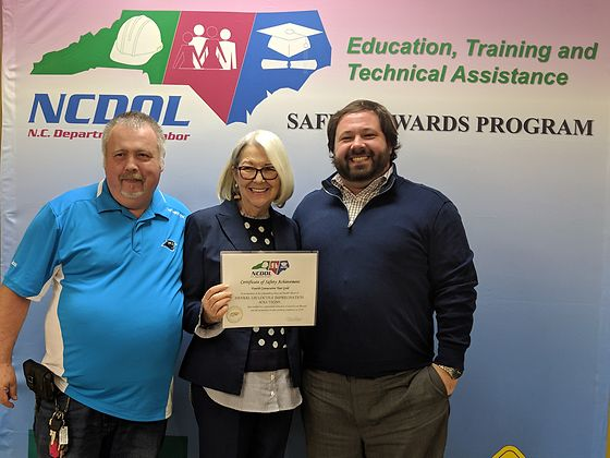 North Carolina Commissioner of Labor Cherie Berry presents the plant's fourth consecutive Gold Certificate of Safety Achievement award to Henkel's Charles McMurry, Jr. (left) and Plant Manager Trent Mason.